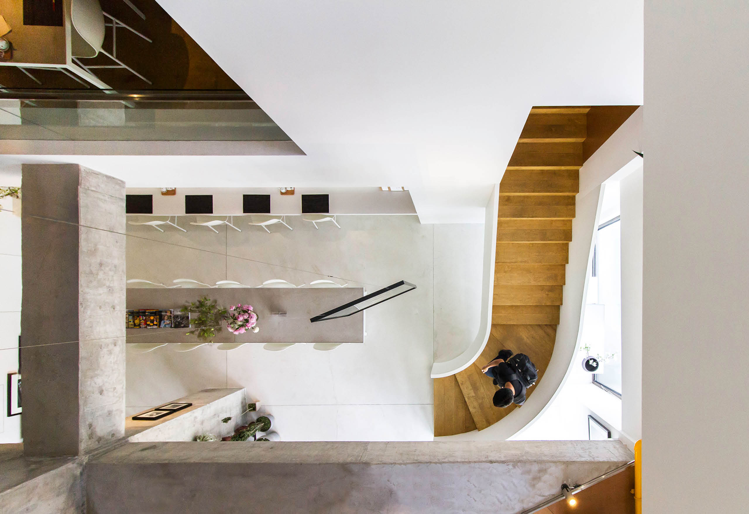 The caramel-colored staircase and other wood elements are a welcome warm contrast to Life As It Is (LAII) Gallery's crisp white scenes.